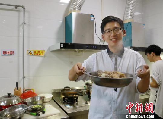 新生何欣佳完成人生中第一道菜——水煮酸菜鱼 魏佩 摄
