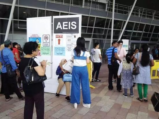 一名考生由家长陪同,进入AEIS考场区域。