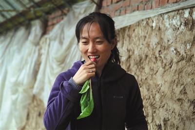 石嫣品尝自己种植的蔬菜。 资料图片