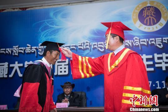 图为西藏大学校长纪建洲(右一)为学位获得者拨流苏。 何蓬磊 摄