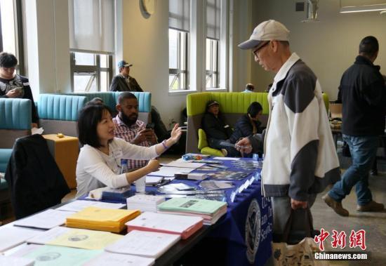资料图:美国移民局官员在为民众提供多种语言的入籍服务。 中新社记者 刘丹 摄