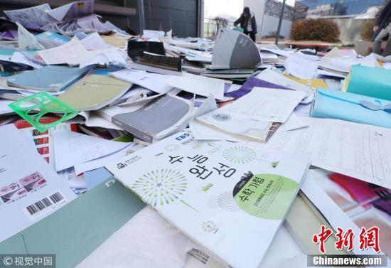 考生在扔掉的书堆中找寻自己的习题册和教科书。