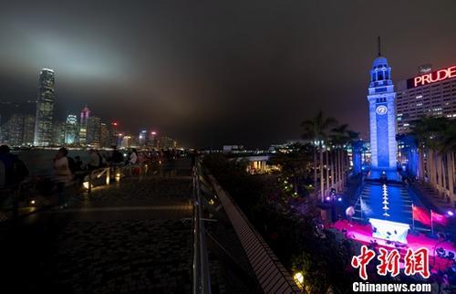 资料图片:香港尖沙咀钟楼亮灯。图为蓝色钟楼与维多利亚港的迷人夜景交相辉映。中新社记者 张炜 摄