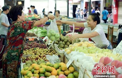 资料图:民众正在购买水果。中新社记者 刘忠俊 摄