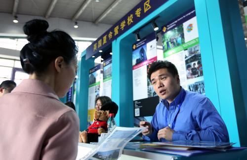 3月24日,英国双子集团的Jason Li(右)向学生家长介绍该校夏令营招生相关事宜。(图片来源:《欧洲时报》特约记者卞正锋摄)