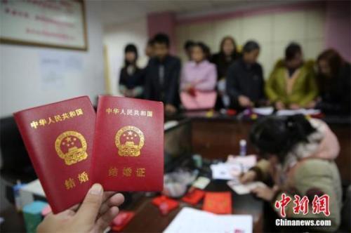 资料图:新人在婚姻登记处展示刚领取的结婚证书。 兰自涛 摄