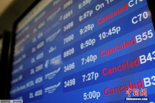 资料图:纽约肯尼迪国际机场航站楼内的电子公告牌。