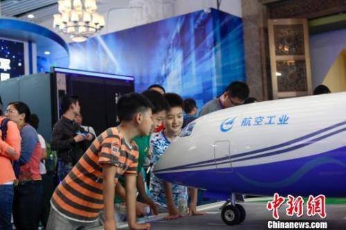 资料图:5月19日,2018年全国科技活动周暨北京科技周活动主场在中国人民革命军事博物馆揭幕。图为展览现场,小观众们正在围观飞机模型。(完) 贾天勇 摄