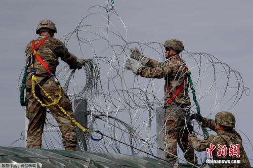 当地时间11月2日,中美洲移民大军压境美国,美国士兵在美墨边境安装铁丝网严防移民入境。