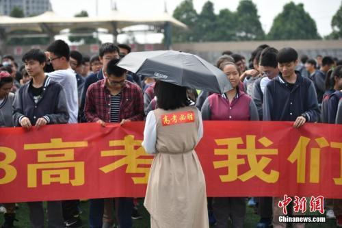 """资料图:2018年6月6日,一名高三老师背后贴着""""高考必胜""""鼓励学生。中新社记者 刘冉阳 摄"""