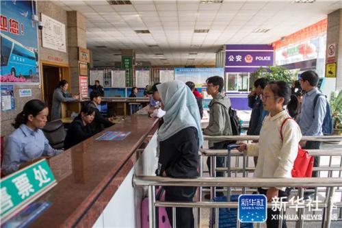 仇文飞在云南省曲靖市会泽县客运站排队购买去昆明的车票(8月30日摄)。新华社记者 胡超 摄