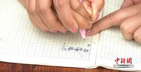 老师教小婷写自己的名字。熊晓华摄