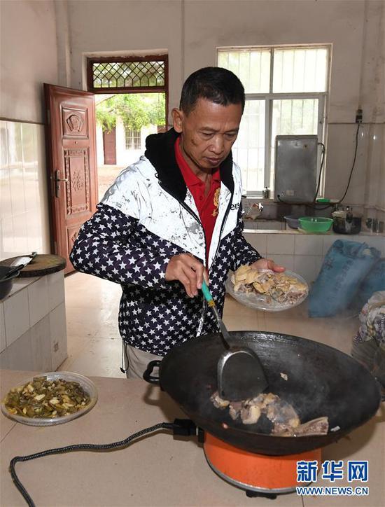 11月19日,在广西上思县那琴乡中心小学逢通村教学点,梁志雄在给学生做午饭。新华社记者陆波岸摄