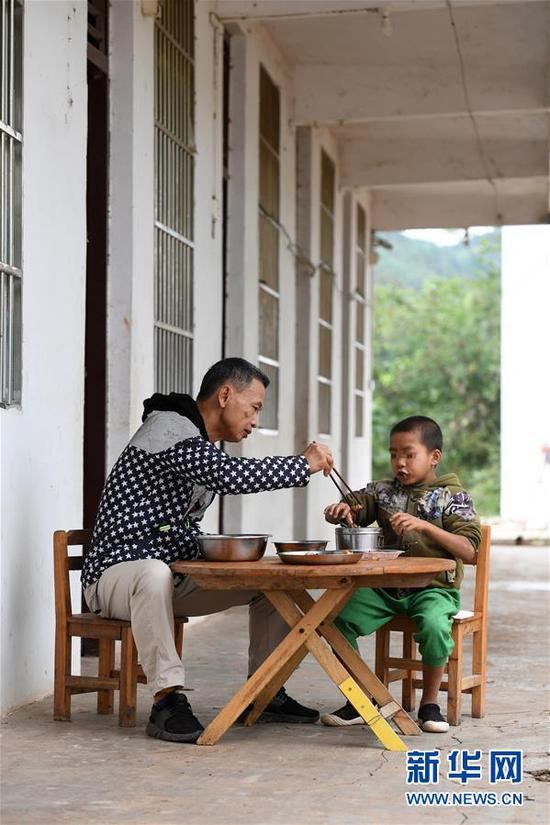 11月19日,在广西上思县那琴乡中心小学逢通村教学点,梁志雄和一名学生吃午饭。新华社记者陆波岸摄
