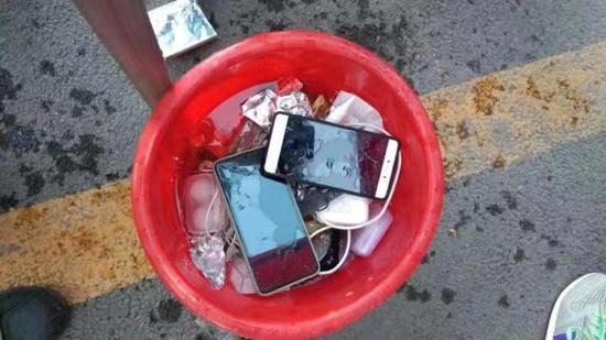 用于销毁手机的盛满水的水桶。  范亭中学官网 图