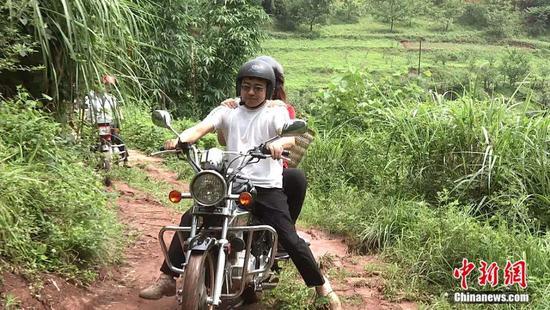 颜志霞乘坐摩托车前往送教。熊晓华摄