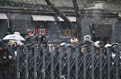 中戏校门外冒雪等待的人们。