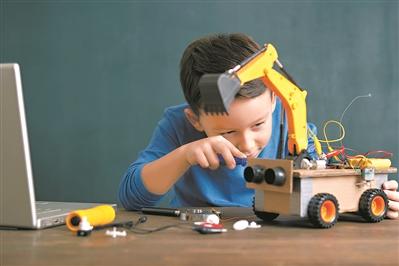 一个孩子正在研究机器人汽车。(图:@视觉中国)