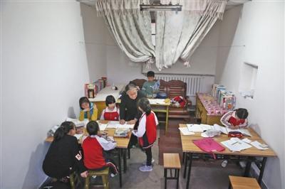严敏文正在指导孩子们学习功课。