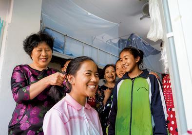 10月1日,在南昌市第十七中学宿舍,刘和平(左一)为一名西藏班学生梳头。