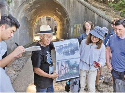 山内正之(左二)在大久野岛上讲解毒气制造相关历史。