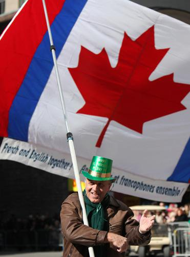 在加拿大魁北克省蒙特利尔市,一名老人扛着象征加拿大的枫叶旗参加游行。(新华社)