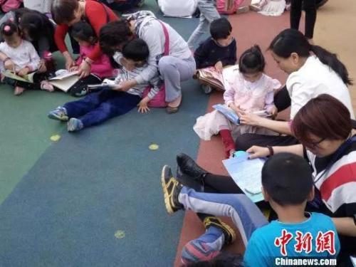 资料图:一家幼儿园内,师生、家长共同和孩子阅读 杨大勇 摄