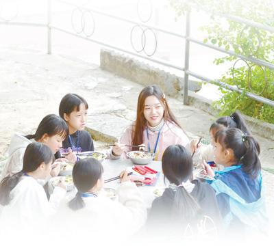 西北工业大学研究生支教团成员与广西融水苗族自治县保桓中学的学生们在校园里吃午饭。新华社记者 黄孝邦摄