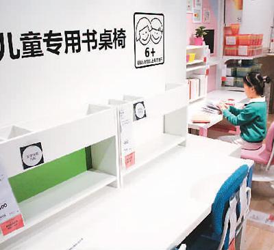 在江苏无锡,小朋友在体验儿童专用书桌椅。资料图片