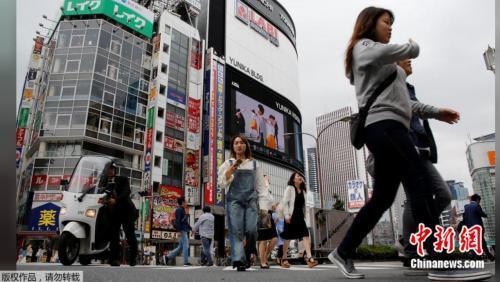 资料图片:2017年5月17日,日本东京新宿商业区,人们穿过街道。