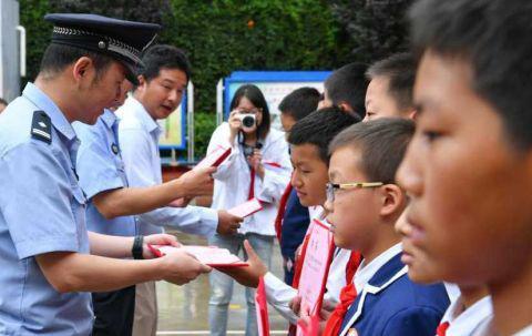 """昆明警方向小学生颁发""""反校园欺凌巡逻队""""聘书。中新社记者 任东摄"""