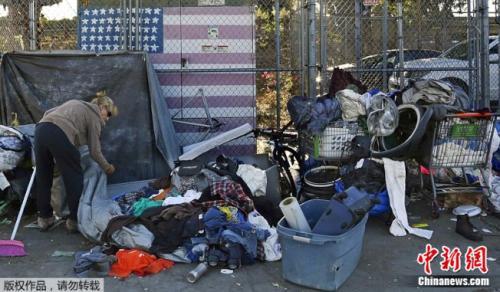 加州房价高涨,约有13.4万人没有住处。图为一名以圣地亚哥街头为家的妇女正在整理她的物品。