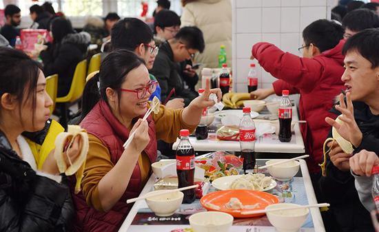 联谊会上,同学开心地吃着饺子。