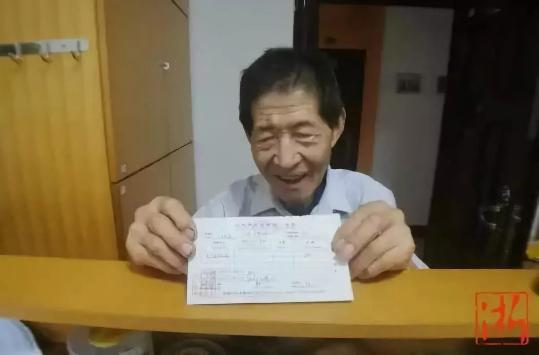 老人高兴地拿着捐款收据。王晨辉 摄