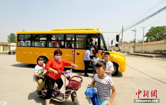 资料图:学生家长接送从校车上下来的学生。 张道正 摄
