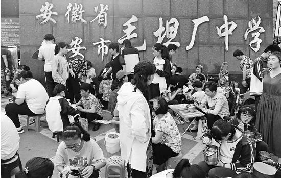 毛坦厂中学的大门口,家长给孩子们送饭。