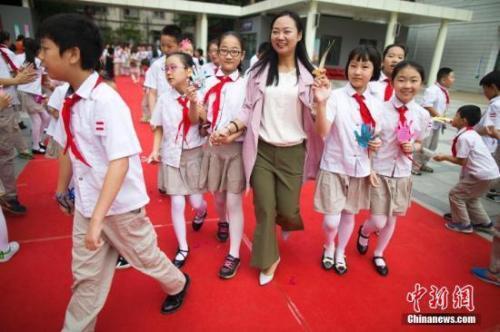 资料图:教师节,老师们牵着学生的手走过红地毯步入校园。张云 摄