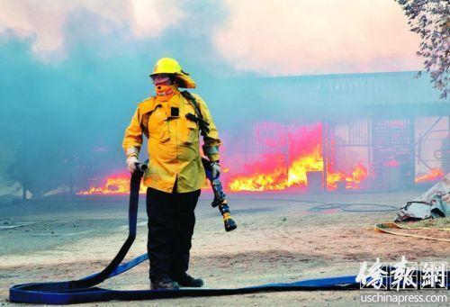 野火中,一位消防员在焦急地等待水源的到来。(美国《侨报》/邱晨 摄)