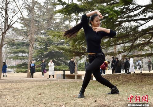 2月27日,北京电影学院2018年艺考初试开考,校园内云集众多高颜值的帅哥美女。图为考场外,有考生进行热身表演,翩翩起舞。 中新网记者 翟璐 摄
