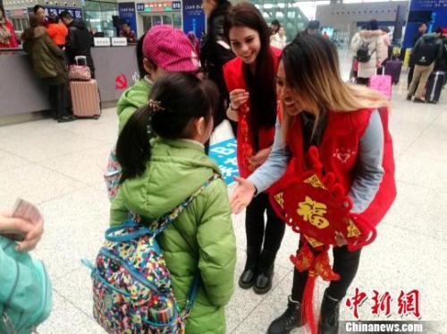 """图为外国留学生志愿者向旅客赠送""""福""""字和中国结。 刘鹏 摄"""