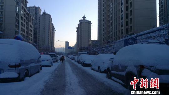 暴雪后的乌鲁木齐清晨,车辆被大雪埋没。