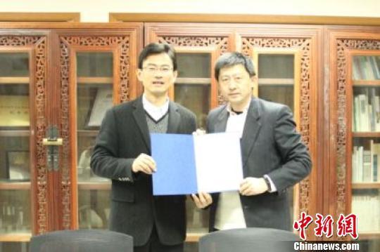 杭州出版社社长童伟中与《华人之光》的作者、波士顿亚美出版社社长李强。杭州出版社 供图