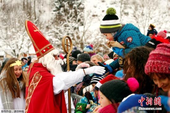 资料图:圣诞老人给孩子们送上礼物。
