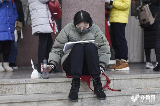 寒冷的冬季,一名女生把自己裹得严严实实,在考点门口外进行最后的复习。