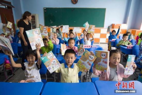 资料图:学生展示教材。张云 摄 中国新闻网