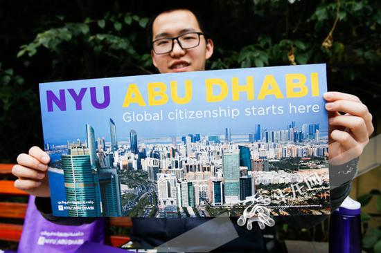 蒋牧颜展示纽约大学阿布扎比分校提供的宣传资料。 记者 石涛 摄