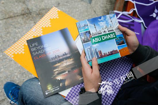 蒋牧颜翻看阿布扎比的城市宣传画册。记者 石涛 摄