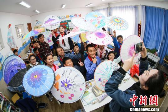 学生向老师展示手绘完成的油纸伞作品。 (解豪 摄)