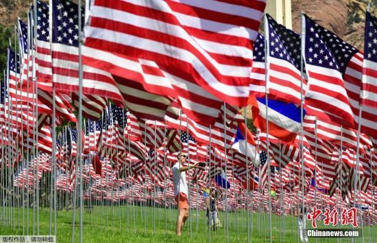 """当地时间2018年9月10日,游客在美国加利福尼亚马里布佩珀丁大学参观""""国旗飘扬""""展览。该展览每年举行,其展出的2997面国旗是为了纪念2001年9月11日""""911""""恐怖袭击的受害者"""