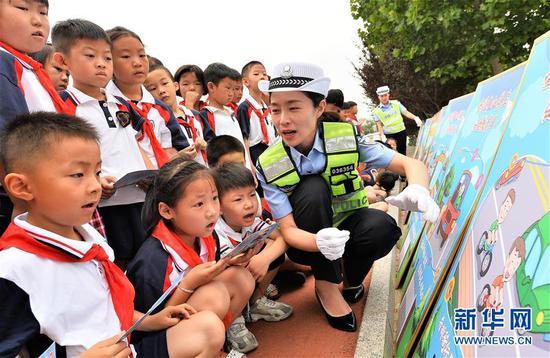 7月4日,山东省枣庄市台儿庄区交警大队民警在给实验小学的学生们讲解交通知识。 暑期来临,各地学校纷纷组织学生开展暑期安全教育主题活动,让孩子们度过一个安全快乐的假期。 新华社发(高启民 摄)